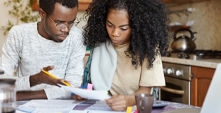 Young couple reviewing student loan debt bills